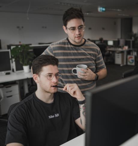 Two men talking at computer