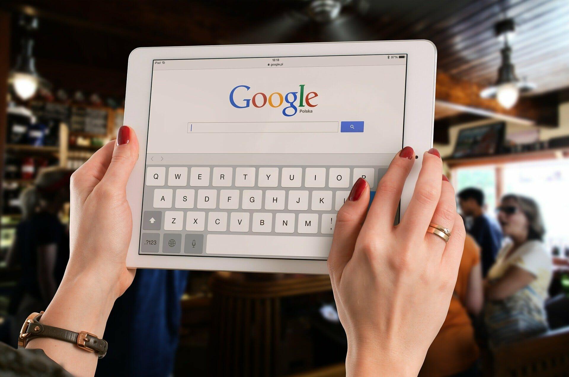 Women holding ipad with google on screen